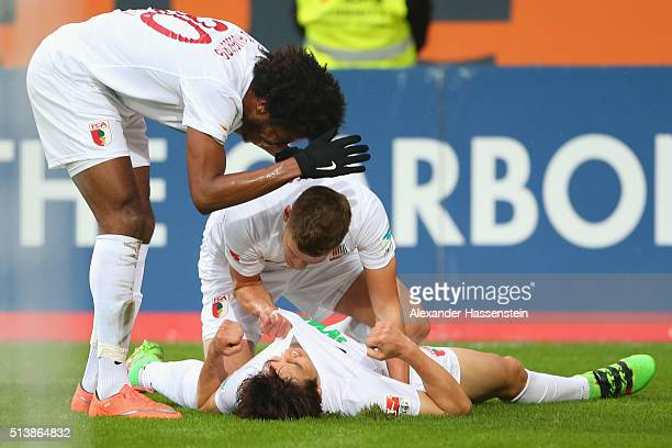 JaCheol Koo of Augsburg celebrates scoring the third goal with his team mate Caiuby Francisco da Silva and Philipp Max during the Bundesliga match...