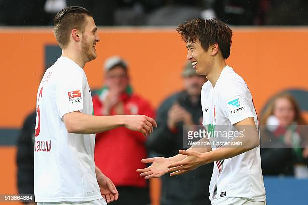 JaCheol Koo of Augsburg celebrates scoring the third goal with his team mate Jeffrey Gouweleeuw during the Bundesliga match between FC Augsburg and...