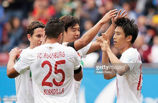 JaCheol Koo of Augsburg is congratulated by JeongHo Hong after scoring a goal during the Bundesliga match between FC Augsburg and 1899 Hoffenheim at...