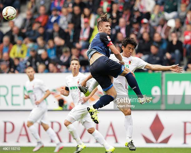 JaCheol Koo of Augsburg is smashed by Ermin Bicakcic of 1899 Hoffenheim during the Bundesliga match between FC Augsburg and 1899 Hoffenheim at...
