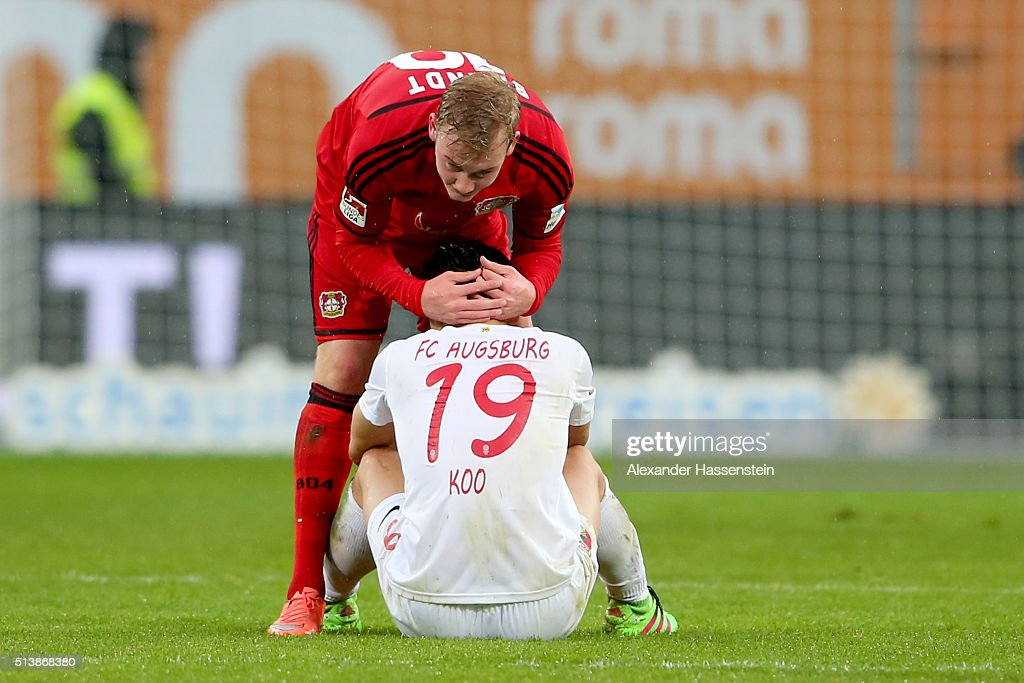 Ja-Cheol Koo (R) of Augsburg reacts with Julian Brandt of Leverkusen after the Bundesliga match between FC Augsburg and Bayer Leverkusen at WWK Arena on March 5, 2016 in Augsburg, Germany.