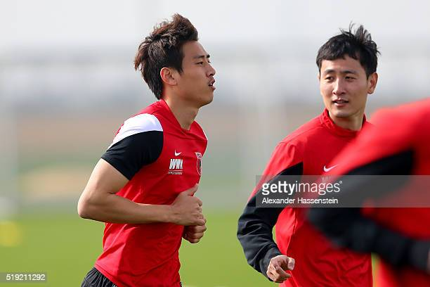 JaCheol Koo of Augsburg runs with his team mate DongWon Ji during a FC Augsburg Training session at WWK Arena on April 5 2016 in Augsburg Germany