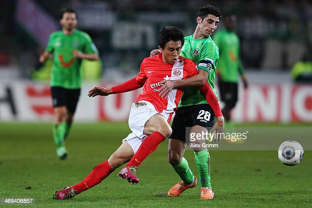 JaCheol Koo of Mainz is challenged by Lars Stindl of Hannover during the Bundesliga match between 1 FSV Mainz 05 and Hannover 96 at Coface Arena on...