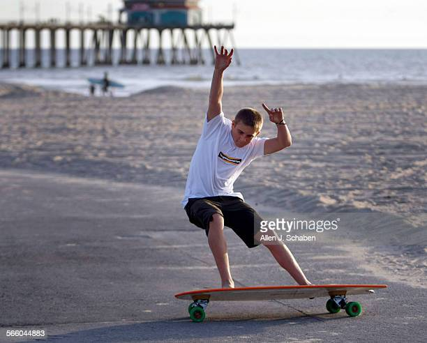 Jachin Hamborg does a tail slide a move that complements his surfing style on a 4'5' Fish Hamboard skateboard along the Huntington Beach bike path...