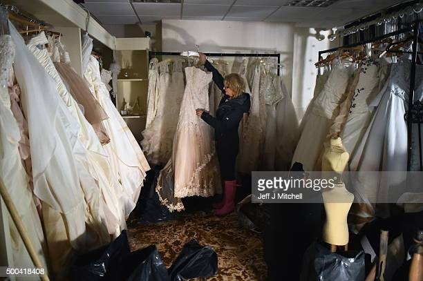 Jacinta Cooper from Kokoabride inspects the damage to bridal dresses in her shop on Warwick Road after Storm Desmond caused flooding on December 8...