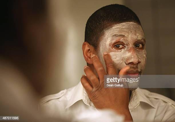 """Jack"""", a cast member of """"GRENZFAeLLE"""", a play that stars African refugees and German actresses, puts on make-up for his role as a white businessman..."""