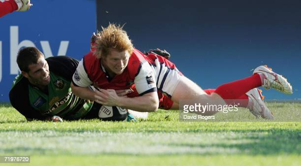 Jack Adams of Gloucester beats Sean Lamont to the ball to score the final try of the match during the Guinness Premiership match between Gloucester...