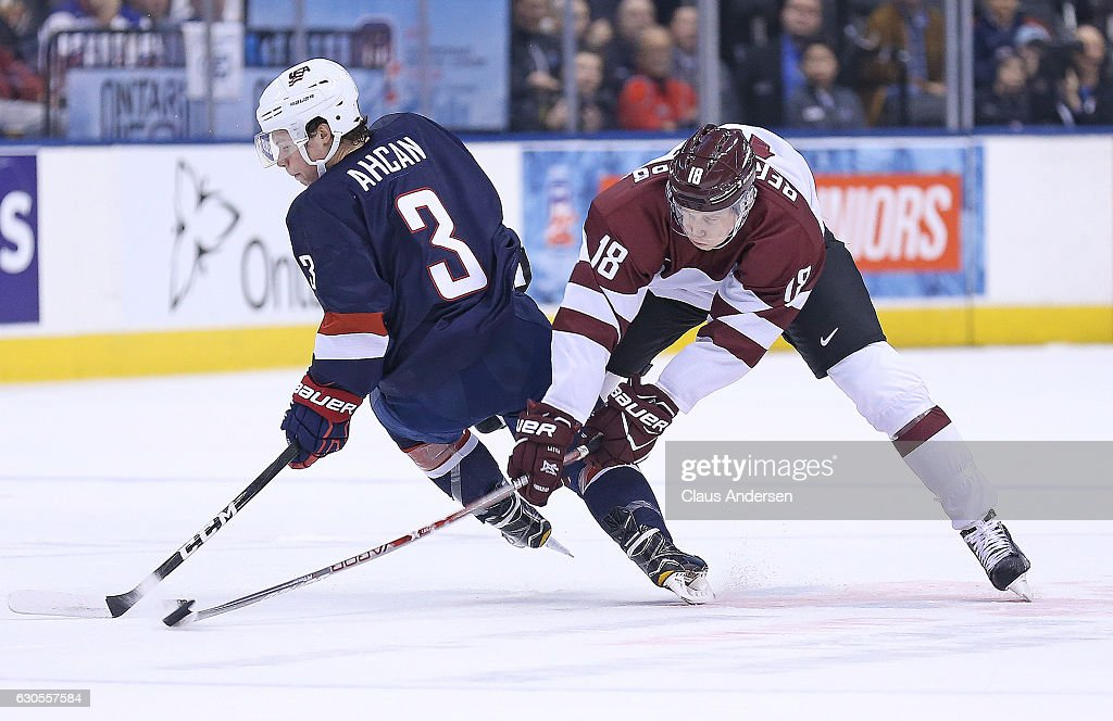 Jack Ahcan #3 of Team USA is knocked off the puck by Ricards Bernhards #18 of Team Latvia during a 2017 IIHF World Junior Hockey Championship game at the Air Canada Centre on December 26, 2016 in Toronto, Ontario, Canada. The USA defeated Latvia 6-1.