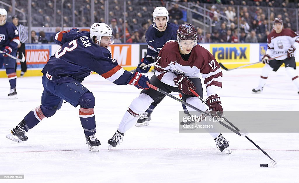 Jack Ahcan #3 of Team USA skates to check Erlands Klavins #12 of Team Latvia during a 2017 IIHF World Junior Hockey Championship game at the Air Canada Centre on December 26, 2016 in Toronto, Ontario, Canada. The USA defeated Latvia 6-1.