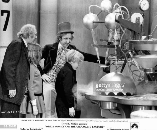 Jack Albertson and Gene Wilder standing by as Peter Ostrum watches candy making machine in a scene from the film 'Willy Wonka the Chocolate Factory'...