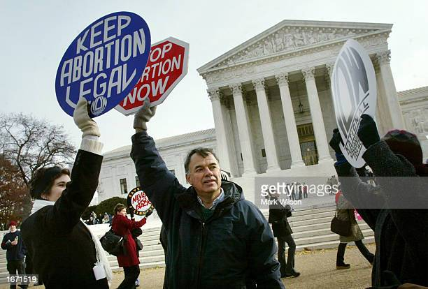 Jack Ames gets his 'Stop Abortion Now' sign blocked by a women holding a 'Keep Abortion Legal' sign during a protest in front of the US Supreme Court...