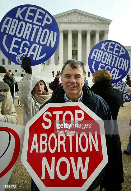 Jack Ames holds his 'Stop Abortion Now' sign next to others holding 'Keep Abortion Legal' signs during a protest in front of the US Supreme Court...