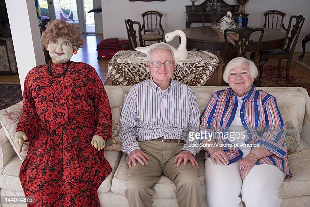 Jack and Lynn Sohm two senior citizens with lifesized doll posing on couch in Annapolis Maryland
