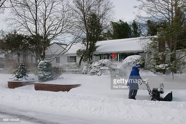 CONTENT] Jack Beebe uses a snow blower to clear the sidewalk in front of his residence in Massapequa NY