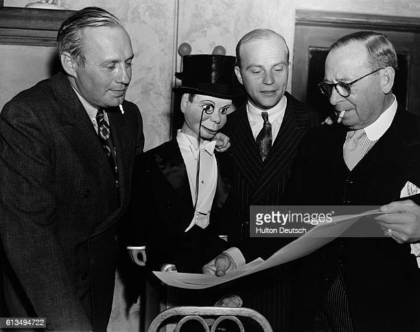 Jack Benny Charlie McCarthy Edgar Bergen and William Collier Sr look over a document