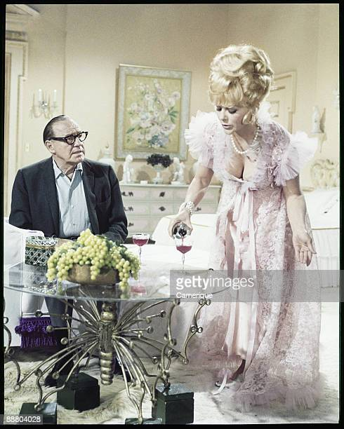Jack Benny sits at a table while Inger Stevens pours him a glass of red wine in this scene from the movie 'A Guide For The Married Man' 1967