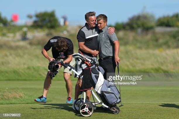 Jack Bigham of Harpenden and his father Andrew embrace after his victory on the 19th green during the Final of the R&A Boys Amateur Championship at...