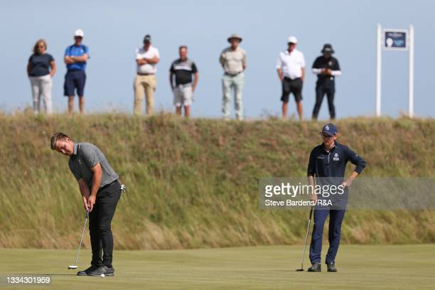 Jack Bigham of Harpenden putts on the 8th green as Riccardo Fantinelli of Italy looks on during the Final of the R&A Boys Amateur Championship at...