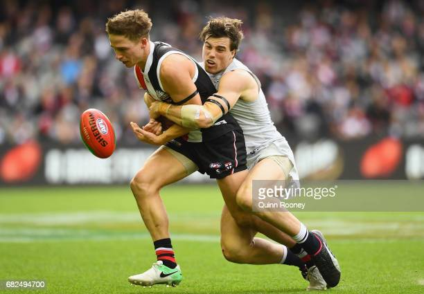 Jack Billings of the Saints handballs whilst being tackled by Lachie Plowman of the Blues during the round eight AFL match between the St Kilda...