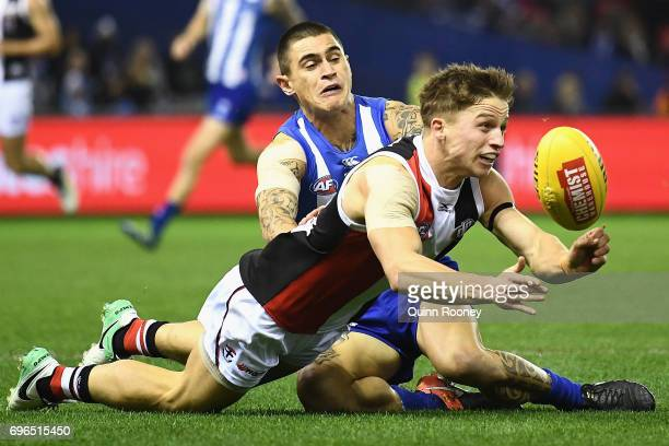 Jack Billings of the Saints handballs whilst being tackled by Marley Williams of the Kangaroos during the round 13 AFL match between the North...