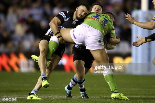 Jack Bird and Chad Townsend of the Sharks tackle Josh Papalii of the Raiders during the round 22 NRL match between the Cronulla Sharks and the...