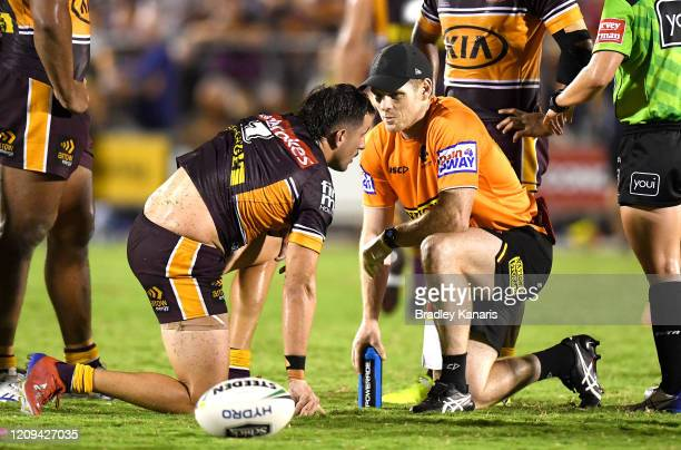 Jack Bird of the Broncos is seen to by a trainer after taking a high shot in the tackle during the NRL Trial match between the Brisbane Broncos and...