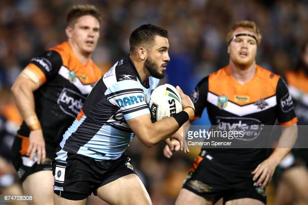 Jack Bird of the Sharks is tackled during the round nine NRL match between the Wests Tigers and the Cronulla Sharks at Leichhardt Oval on April 29...