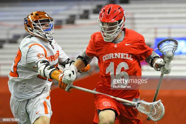 Jack Bolen of the Cornell Big Red runs with the ball as Stephen Rehfuss of the Syracuse Orange throws a check during a 2018 NCAA Division I Men's...