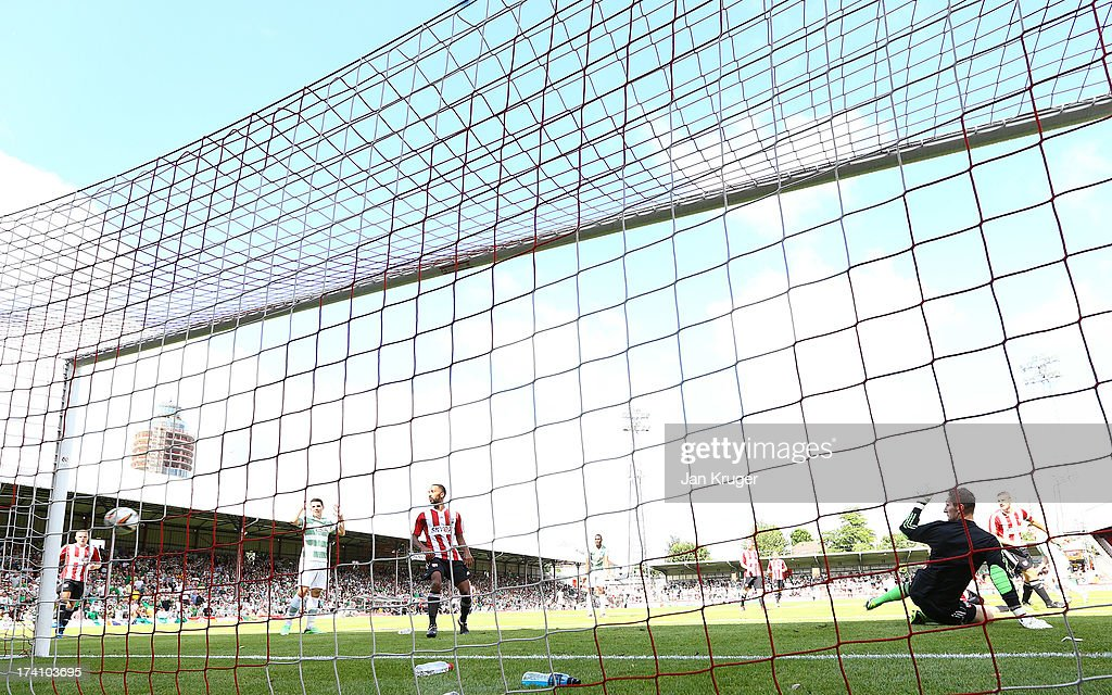 Jack Bonham, Goalkeeper of Brentford(R) sees the shot at goal from Callum McGregor of Celtic find the back of the net during a pre season friendly match between Brentford and Celtic at Griffin Park on July 20, 2013 in Brentford, England.