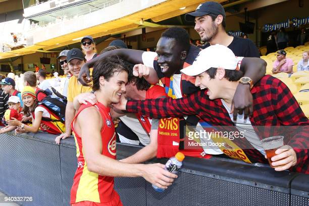 Jack Bowes of the Suns celebrates the win with fans after winning during the round two AFL match between the Carlton Blues and the Gold Coast Suns at...