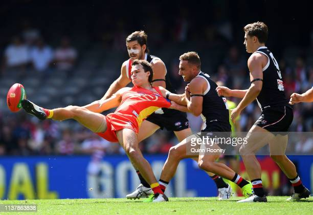 Jack Bowes of the Suns kicks whilst being tackled by Luke Dunstan of the Saints during the round one AFL match between the St Kilda Saints and the...