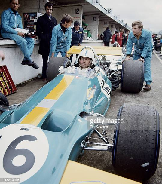 Jack Brabham aboard the Motor Racing Developments Brabham BT33 Ford Cosworth DFV 30 V8 waits in the pits as his mechanics overseen by Ron Dennis...