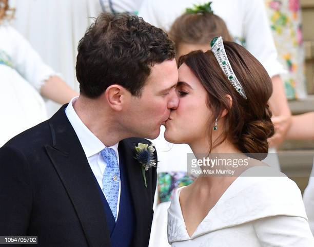 Jack Brooksbank and Princess Eugenie kiss as they leave St George's Chapel following their wedding ceremony on October 12 2018 in Windsor England