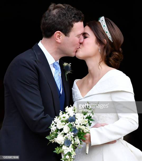 Jack Brooksbank and Princess Eugenie of York share a kiss as they leave their wedding at St George's Chapel on October 12 2018 in Windsor England