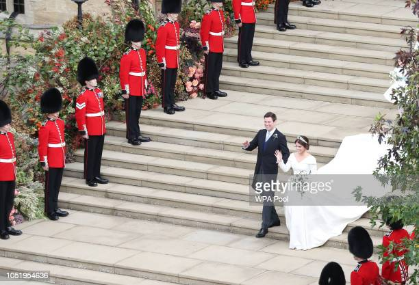 Jack Brooksbank and Princess Eugenie of York walk down the steps after their wedding ceremony at St George's Chapel on October 12 2018 in Windsor...