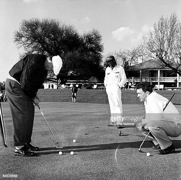 Jack Burke Jr watches Ben Hogan putt on the practice green with the Clubhouse in the background during the 1960 Masters Tournament at Augusta...