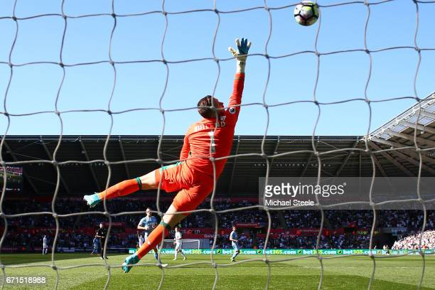 Jack Butland of Stoke City attempts to save as Tom Carroll of Swansea City scores his sides second goal during the Premier League match between...