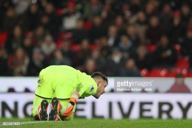 Jack Butland of Stoke City feels the effects of Kevin De Bruyne of Manchester City catching his ankle during a 50/50 battle for the football during...