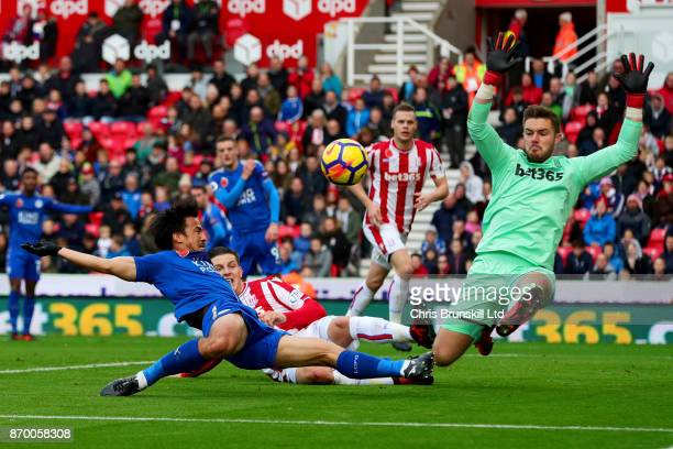 Jack Butland of Stoke City in action with Shinji Okazaki of Leicester City during the Premier League match between Stoke City and Leicester City at...