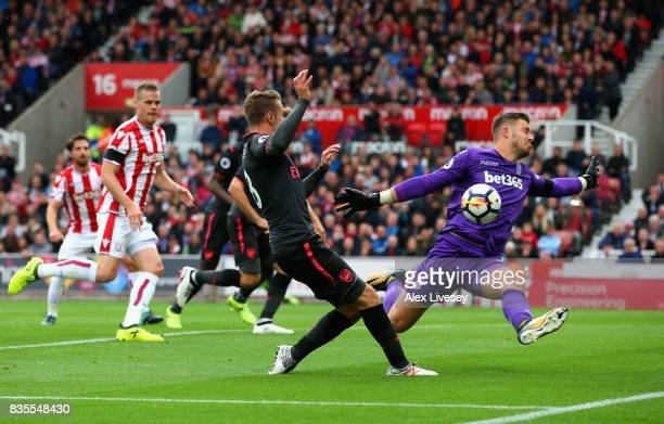 Jack Butland of Stoke City saves from Aaron Ramsey of Arsenal during the Premier League match between Stoke City and Arsenal at Bet365 Stadium on...