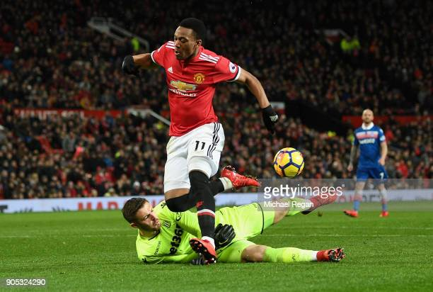 Jack Butland of Stoke City tackles Anthony Martial of Manchester United during the Premier League match between Manchester United and Stoke City at...