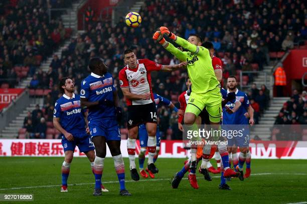 Jack Butland of Stoke punches the ball away under pressure from Oriol Romeu of Southampton during the Premier League match between Southampton and...