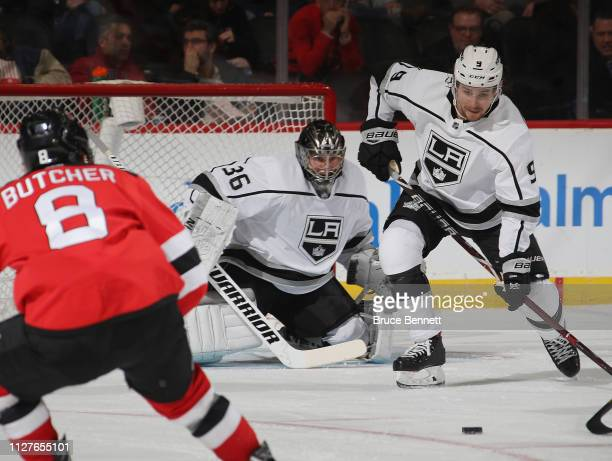 Jack Campbell and Adrian Kempe of the Los Angeles Kings defend the net against Will Butcher of the New Jersey Devils during the first period at the...