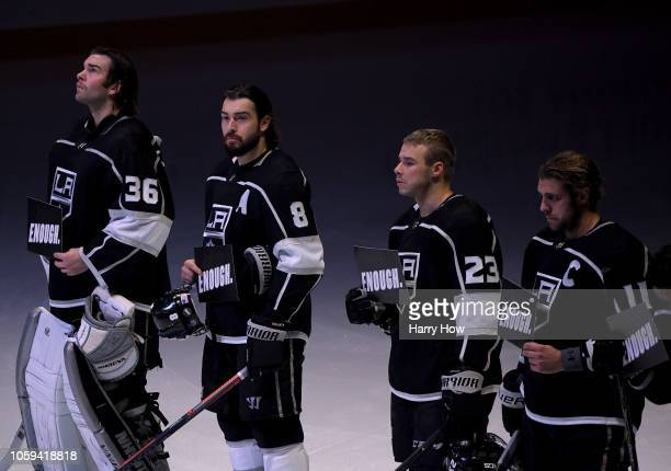 "Jack Campbell, Drew Doughty, Dustin Brown and Anze Kopitar of the Los Angeles Kings hold up signs with the word ""ENOUGH"" in reaction to yeserday's..."