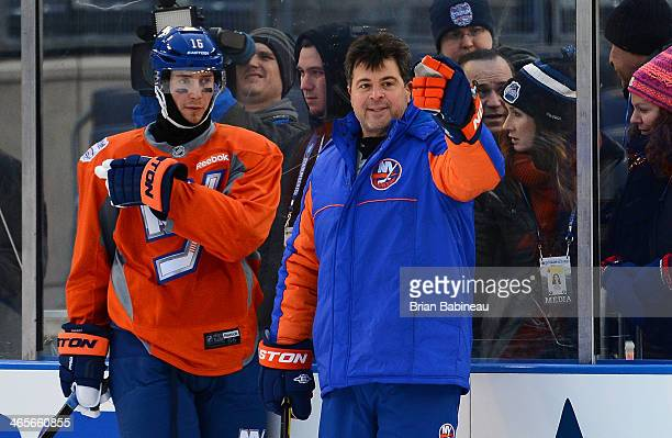 Jack Capuano of the New York Islanders speaks with Peter Regin during the 2014 NHL Stadium Series practice session at Yankee Stadium on January 28...