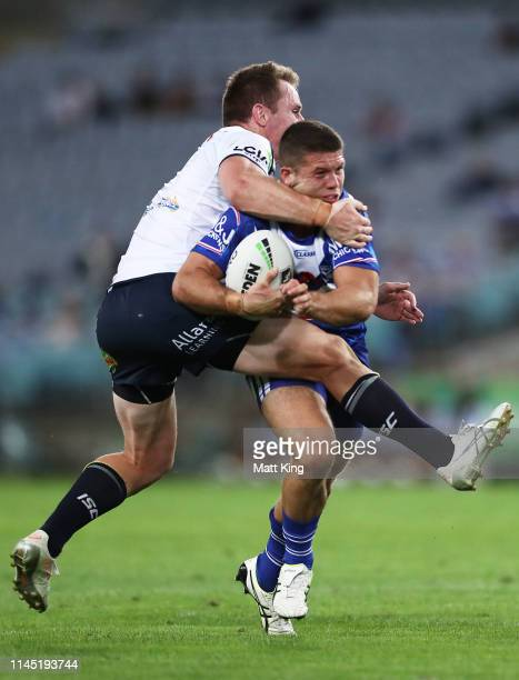 Jack Cogger of the Bulldogs is tackled by Michael Morgan of the Cowboys during the round 7 NRL match between the Canterbury Bulldogs and the North...