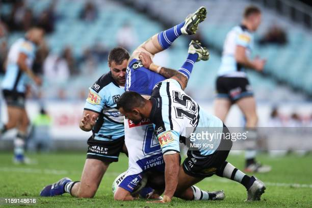 Jack Cogger of the Bulldogs is tackled during the round 15 NRL match between the Canterbury Bulldogs and the Cronulla Sharks at ANZ Stadium on June...