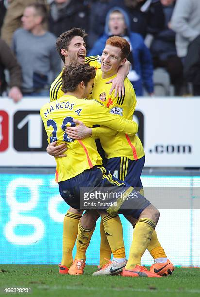 Jack Colback of Sunderland is congratulated by teammates Marcos Alonso and Fabio Borini after scoring his team's third goal during the Barclays...