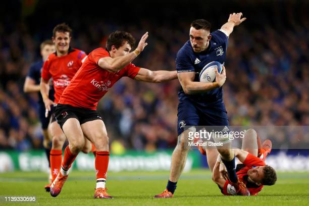 Jack Conan of Leinster breaks the tackle of Michael Lowry and Jacob Stockdale of Ulster during the Champions Cup Quarter Final match between Leinster...