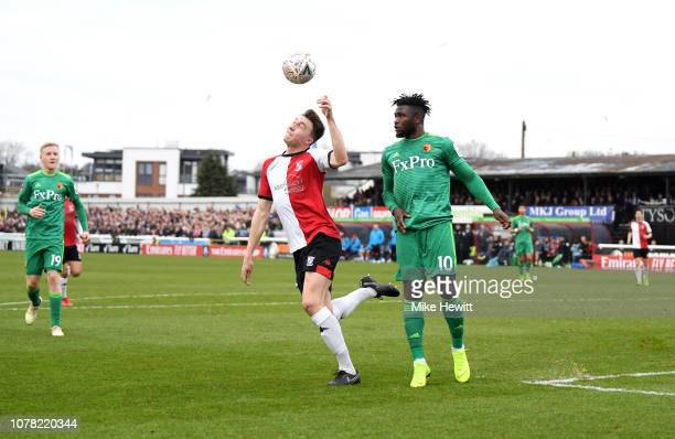 Jack Cook of Woking is fouled by Isaac Success of Watford during the FA Cup Third Round match between Woking and Watford at Kingfield Stadium on...